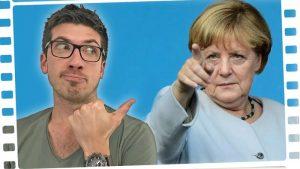 Ein Mann mit kurzen Haaren und Brille (links) deutet auf Angela Merkel, die mit dem Zeigefinger nach vorne zeigt.