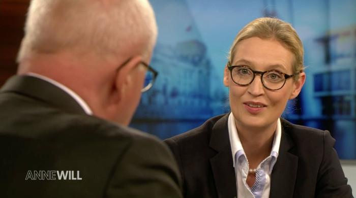 Frau mit zusammengebundenen Haaren, zusammengebunden, Brille, weißer Bluse Perlenkette und schwarzem Blazer redet mit einem Mann, der von hinten im Anschnitt zu sehen ist.