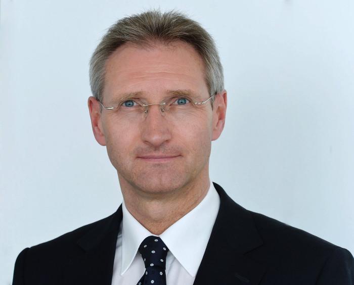 Mann mit randloser Brille, leicht angegrautem Haar und schwarzem Anzug mit Krawatte schaut in die Kamera