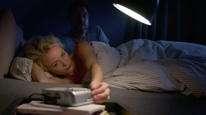 Standbild aus dem Imagefilm der Funke Mediengruppe: Ein Ehepaar im Bett, es ist Morgen. Die Frau schaltet den Wecker aus, der Mann richtet sich im Hintergrund auf.