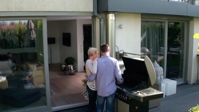 Standbild aus dem Imagefilm der Funke Mediengruppe: Mann und Frau stehen auf einer Terrasse an einem großen Grill, Arm in Arm. Der Mann grillt.