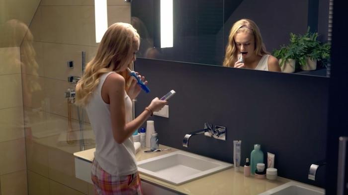 Standbild aus dem Imagefilm der Funke Mediengruppe: Eine Teenagerin steht im Bad, putzt sich die Zähne und liest dabei auf dem Smartphone.