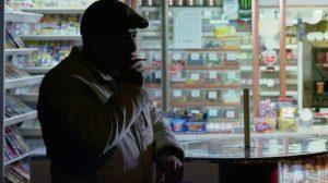Standbild aus dem Imagefilm der Funke Mediengruppe: Ein Mann steht im Halbdunkel vor einem Kiosk und zieht an einer Zigarette.