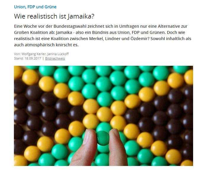 Jemand hält ein grünes M&M vor einer Jamaika-Flagge, die aus M&Ms gebastelt wurde