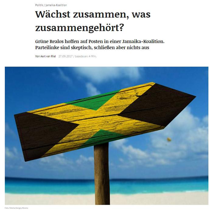Holzschild am Strand mit aufgemalter Jamaika-Flagge