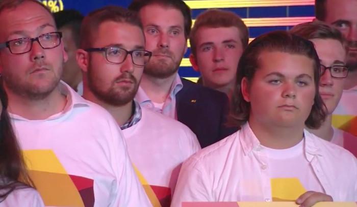 """Mehrere junge Menschen schauen gelangweilt aus ihren CDU-Wahlshirts. Nicht im Bild: Einer hält ein Schild mit der Aufschrift """"Voll muttiviert""""."""