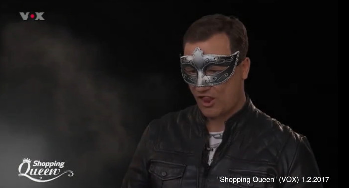 Guido Maria Kretschmer sitzt mit silberner Maske und Lederjacke vor der Kamera und streckt leicht die Zunge raus.