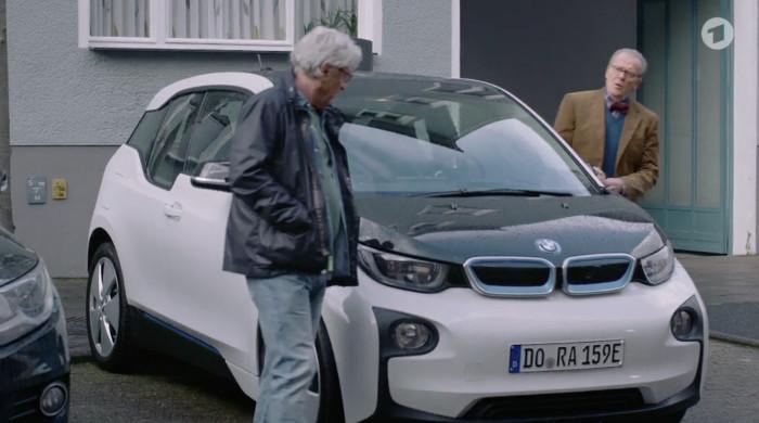 """Szene aus der """"Lindenstraße"""" (Das Erste) vom 30.4.2017. Zu sehen sind zwei Männer, die um ein Elektroauto herum gehen."""