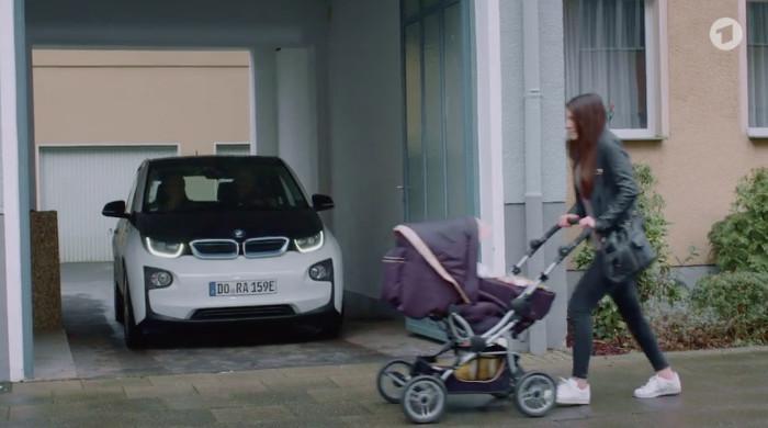 """Szene aus der """"Lindenstraße"""" (Das Erste) vom 30.4.2017. Zu sehen ist ein Auto, das aus einer Ausfahrt fährt, davor läuft eine Frau mit Kinderwagen."""