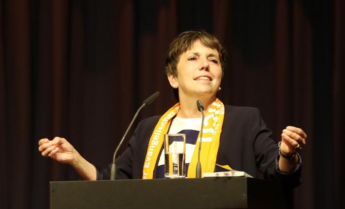Margot Käßmann steht hinter einem Pult und redet
