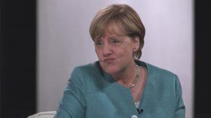 Angela Merkel zieht die Mundwinkel nach unten zum Gesicht eines schlecht gelaunten Smileys