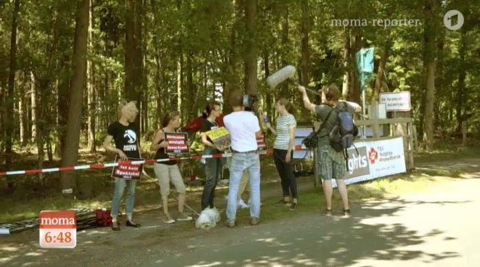 Reporterin und Kamerateam stehen vor vier Demonstranten mit Schildern und interviewen sie.