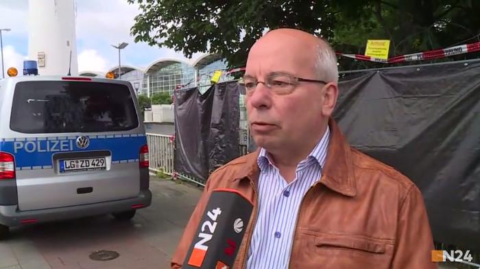 Rainer Wendt im Interview mit N24: Mann, Glatze, Brille, braune Lederjacke, blaues Hemd, steht vor einem Polizeiwagen.