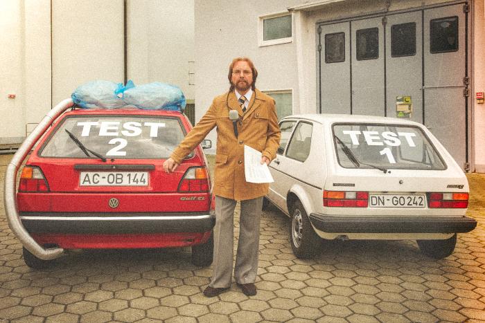"""Sigmar Seelenbrecht steht vor zwei Autos (Golf) der frühen Gerneration, der rote ist mit """"Test 2"""" beschriftet auf der Heckscheibe, der rote mit """"Test 1""""."""