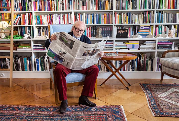 Sigmar Seelenbrecht sitzt in seiner Berliner Wohnung vor einer Bücherwand und liest Zeitung