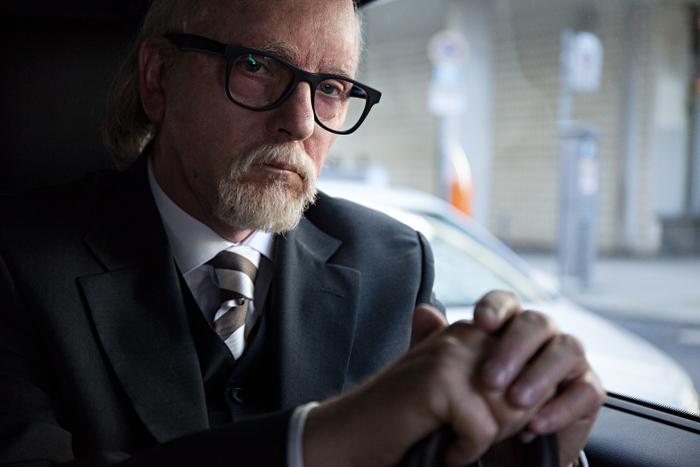 Sigmar Seelenbrecht im Anzug mit gestreifter Krawatte, Brille und weißem Kinn- und Oberlippenbart.