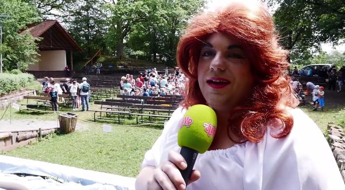 """Standbild aus einem MDR-Clip der Serie """"Sommer bei uns"""", zu sehen ist ein als Frau verkleideter Mann, mit Kleid und roter Perücke, der ein Mikrofon des Senders MDR Jump in Händen hält."""