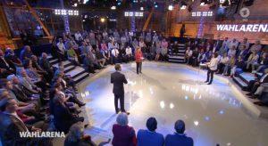 Studioansicht von oben: Zuschauer sitzen auf Tribünen um Angela Merkel und die beiden Moderatoren herum.