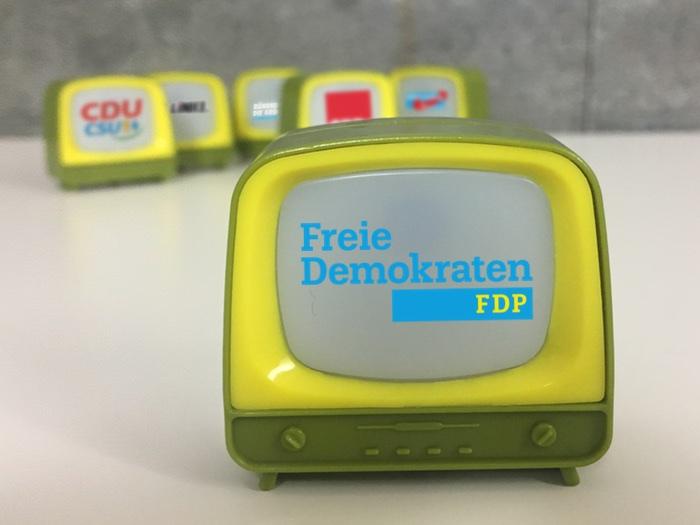 Kleiner Fernseher mit dem Logo der FDP vorne und im Hintergrund fünf weitere Fernseher mit den Logos der SPD, Union, Grünen, Linken und AfD.