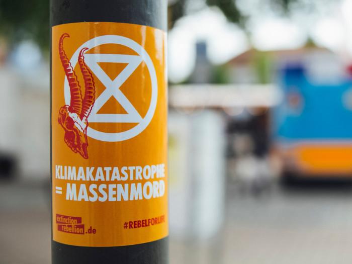 """Ein Sticker von Extinction Rebellion mit der Aufschrift """"Klimakatastrophe = Massenmord"""""""