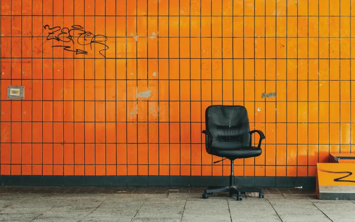 Ein leerer Bürostuhl vor einer orange gekachelten Wand