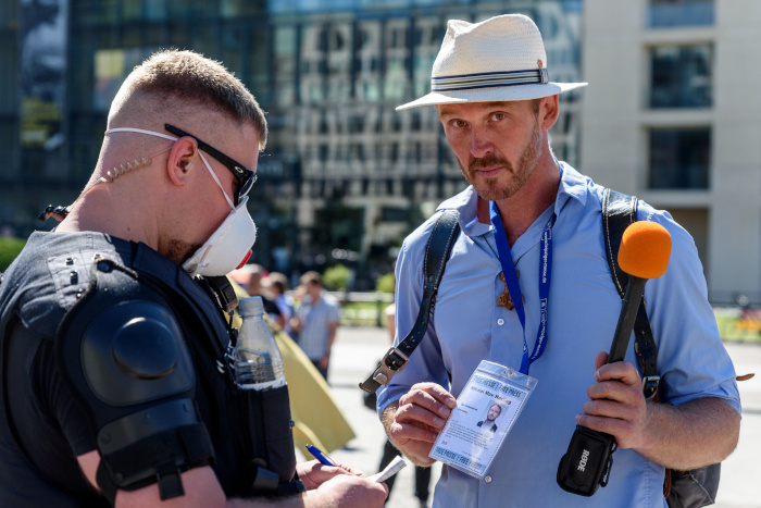 """Der sich selbst """"Volkslehrer"""" nennende Nikolai Nerling wird auf einer Demo am 1. August in Berlin von einem Polizisten kontrolliert"""