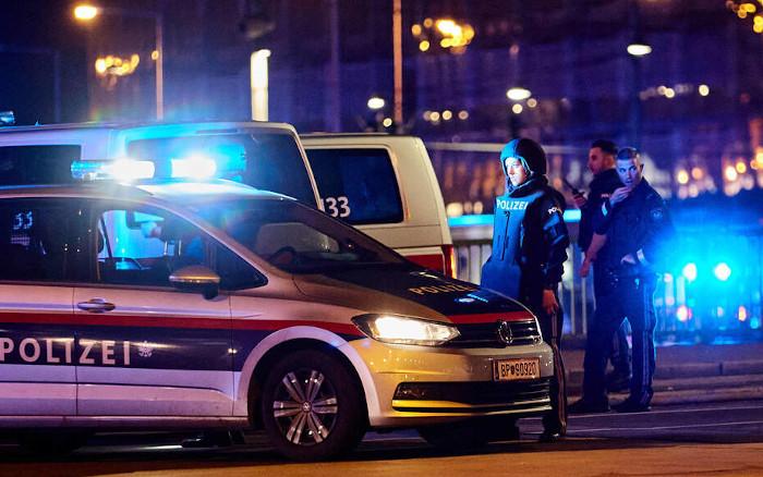 Polizisten stehen neben einem Einsatzwagen in Wien in der Nacht vom 2. auf den 3. November 2020