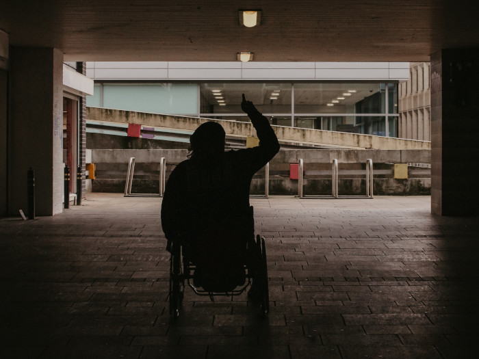 Ein Mann im Rollstuhl zeigt den Mittelfinger