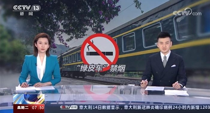 Eine Nachrichtensprecherin und ein Nachrichtensprecher im chinesischen Fernsehen, im Hintergrund ein Rauchverbotsschild und ein Zug, links oben das Senderlogo CCTV-13