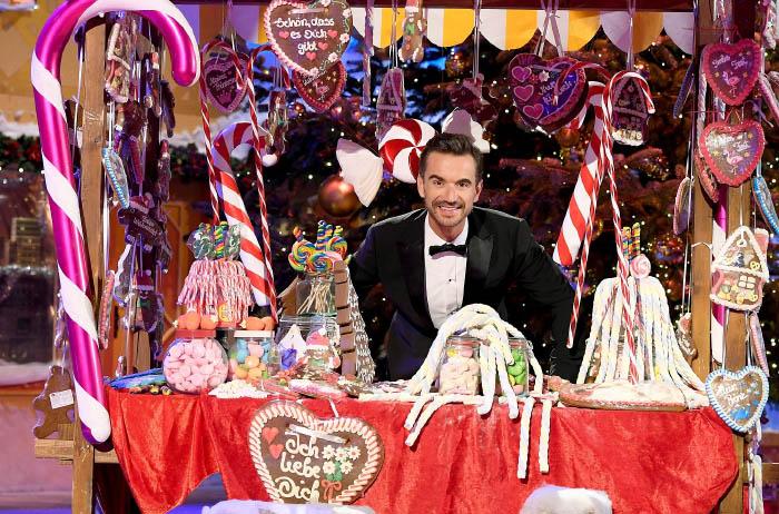 """Florian Silbereisen steht im weihnachtlich geschmückten Studio an einem Süßigkeitenstand, an dem u.a. Lebkuchenherzen mit Aufschriften wie """"Ich liebe Dich"""" hängen"""