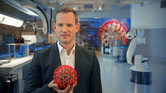 Hendrik Streeck hält ein großes Corona-Virus in der Hand