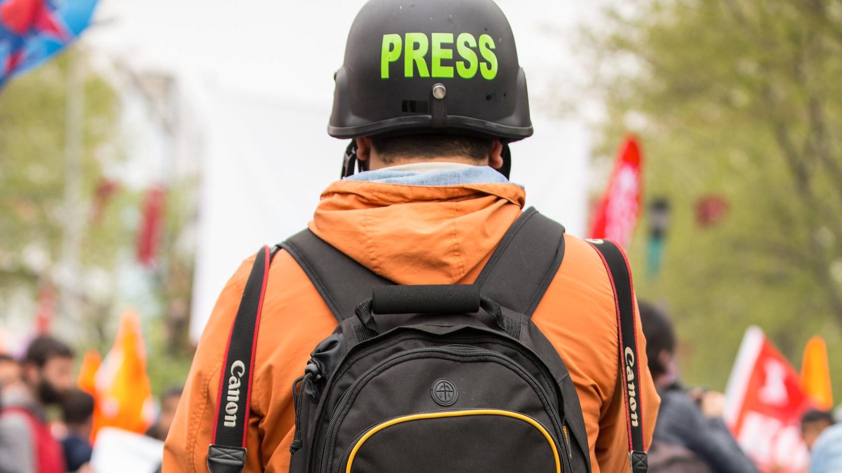 Ein Journalist mit Helm auf dem Kopf auf einer Demo