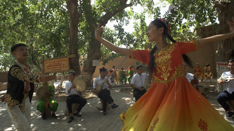 Ein folkloristischer Tanz in der Provinz Xinjiang