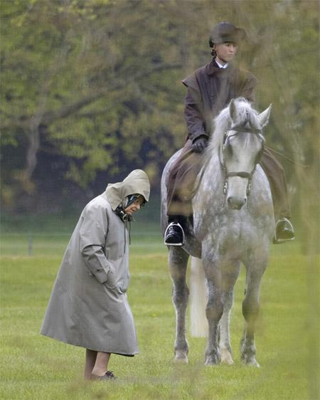 [Die Queen geht in Regenkleidung über eine Wiese, wenige Meter von ihr entfernt steht ein Pferd mit einer Reiterin im Sattel]