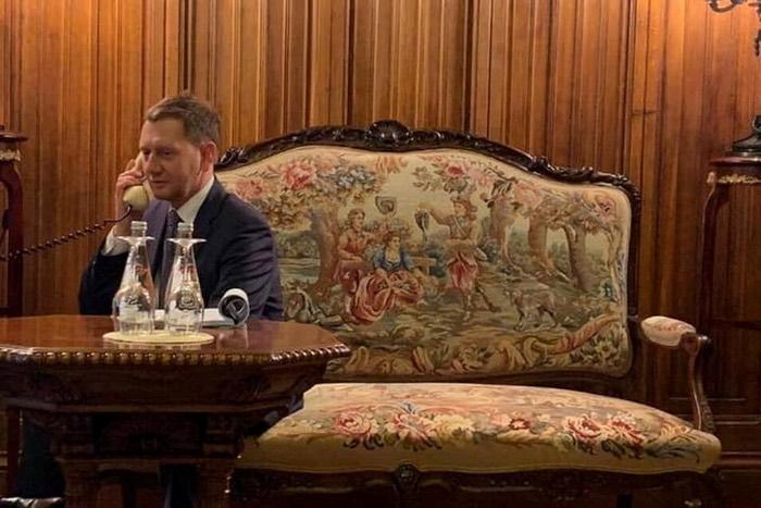 Michael Kretschmer sitzt am Rande des Bildes auf einem Sofa und telefoniert