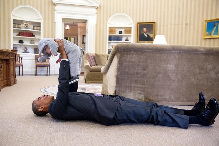 Obama liegt auf dem Boden im Oval Office und hält ein Kind hoch