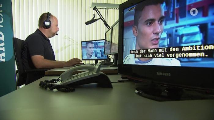 Mann mit Headset sitzt vor Bildschrimen