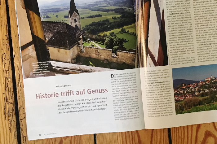"""Reise-Reportage in der Zeitschrift """"ACE Lenkrad"""" über die Region Mittelkärnten. Auf dem Foto ist eine Kirche in grüner Landschaft zu sehen. Überschrift: """"Historie trifft auf Genuss""""."""