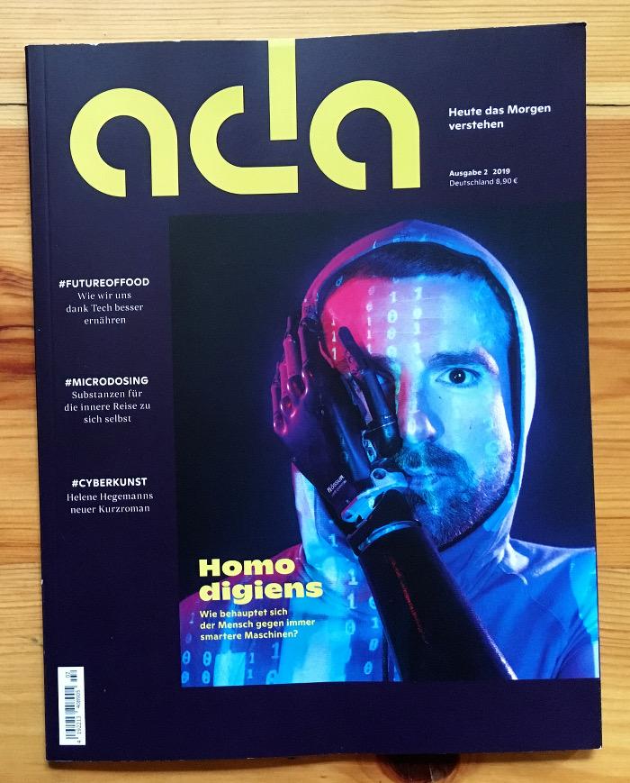 Zeitschriftentitel mit einem Mann, der eine Kapuze trägt und einen Roboterarm im Gesicht hat.