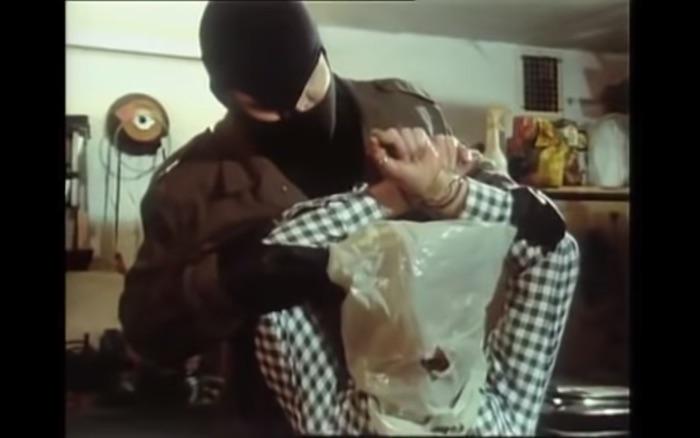 Maskierter Mann bedrängt einen anderen Mann, dem er eine Tüte über den Kopf gezogen hat.