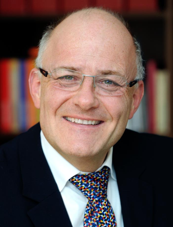Mann mit Brille, Anzug und Krawatte lächelt in die Kamera