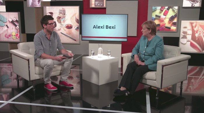 Ein Fernsehstudio mit mehreren Monitoren im Hintergrund, die verschiedene Dinge zeigen, unter anderem Nagellackflaschen, eine Teetasse, Schuhe und so weiter. links sitzt ein dunkelhaariger Mann mit Brille in einem Sessel, neben ihm Angela Merkel im grünen Blazer.