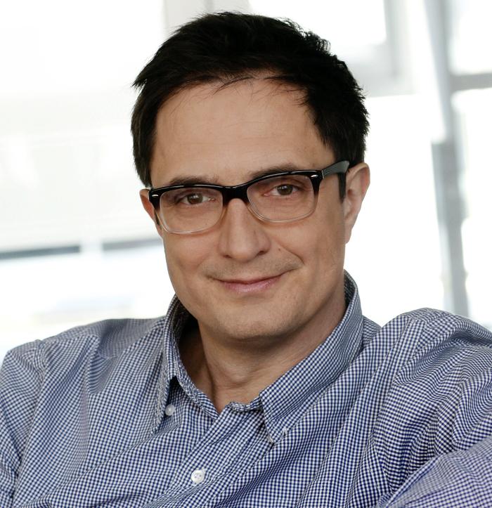 Mann mit Brille, kurzen dunklen Haaren und fein kariertem Hemd.