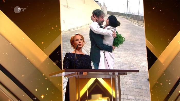"""Julia Becker steht auf der Bühne der """"Goldenen Kamera"""" am Rednerpult, hinter ihr ein großes Foto von Deniz Yücel, der nach der Freilassung aus dem Gefängnis seine Frau umarmt"""