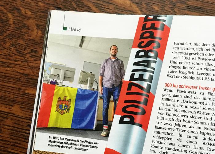 Mann steht vor einem Schreibtisch, an den er eine Flagge von Moldawien gehängt hat