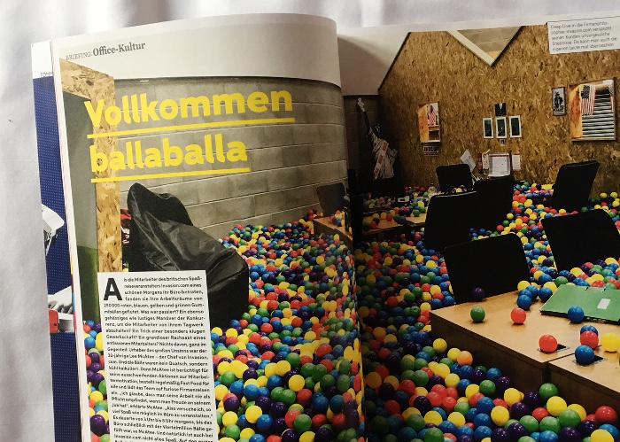 """Büro voller bunter Bälle um die Tische und Stühle, Überschrift: Vollkommen ballaballa"""""""