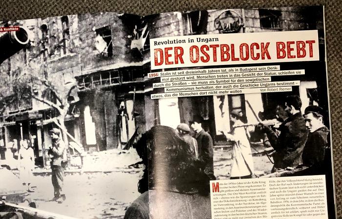 """Überschrift: """"Der Ostblock bebt"""" auf einem Foto, schwarz-weiß, das eine Straße zeigt, Männer mit Gewehren und ein Panzerrohr."""
