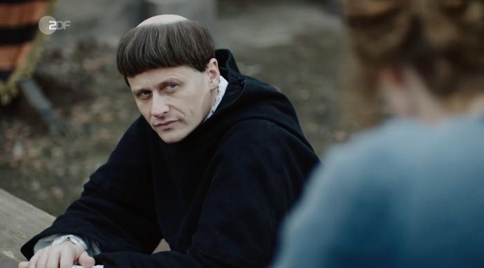 Luther sitzt auf einer Bank und schaut grimmig.
