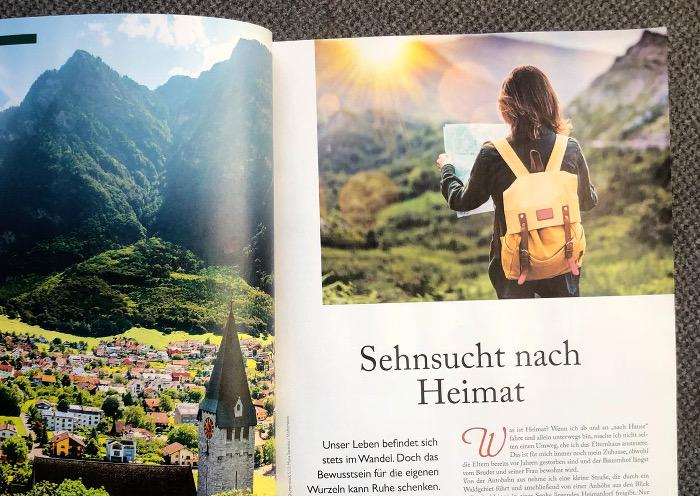 """Linke Seite: Blick auf ein Dorf in einem Tal, rechte Seite: Eine Frau mit Rucksack schaut auf eine Karte, Schlagzeile: """"Sehnsucht nach Heimat"""""""