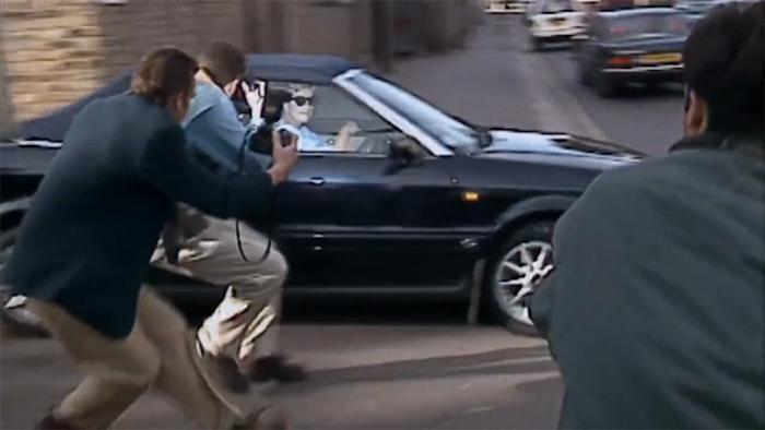 Prinzessin Diana sitzt in ihrem Auto, will wegfahren, als mehrere Paparazzi mit Kameras auf das Auto zustürmen.